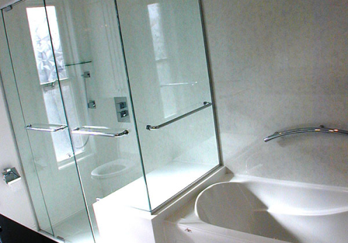 Custom glass panels on a Corian seat with shower bars and a swinging door