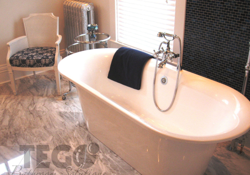 Proud free-standing tub with hand shower and spout with a mosaic tile wall